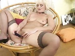 Mature mother is feeding her aged pussy crevasse with a smallish nasty dildo